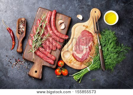 Sausages, meat and ingredients for cooking. Top view on stone table