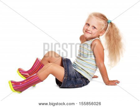 Smiling little blond girl in a skirt and blouse, rubber boots sitting isolated on white background.