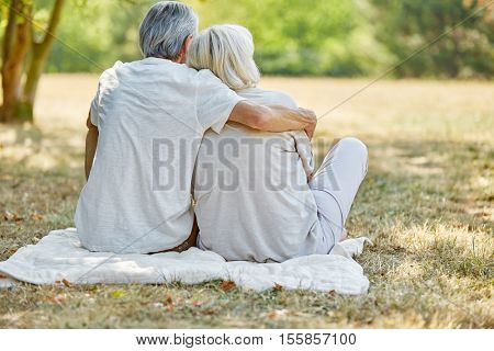 Happy senior couple in love sitting in the garden in summer