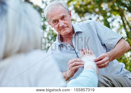 Senior man puts a bandage on a woman's sprainded ankel in the park