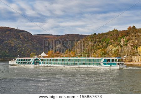 BOPPARD, GERMANY - NOVEMBER 06, 2016: Rhein tour ship Amadeus Princess passes Boppard in front of autumn colored hills