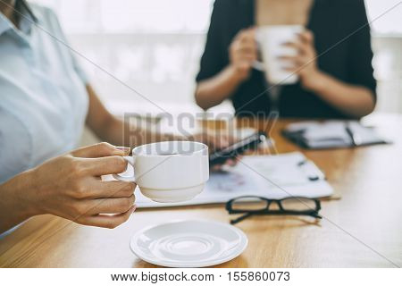 businesswomen working in office with coffee and smartphone