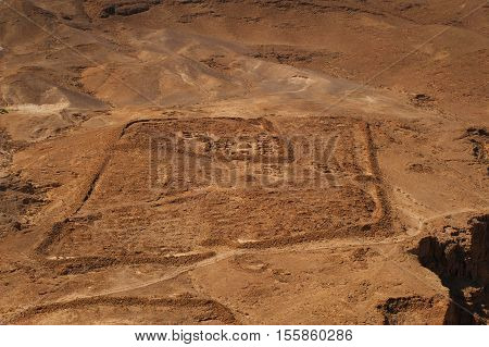 Top view from Masada fortress to the Judean desert. The ruins of the Roman camp