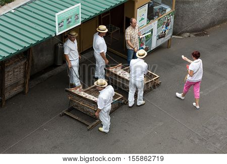 FUNCHAL, MADEIRA, PORTUGAL - SEPTEMBER 2, 2016: Toboggan riders moving traditional cane sledge downhill on the streets of Funchal. Monte park Madeira island Portugal