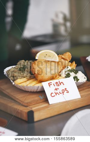 Crispy fish and chips with peas and lemon street food outdoors food concept