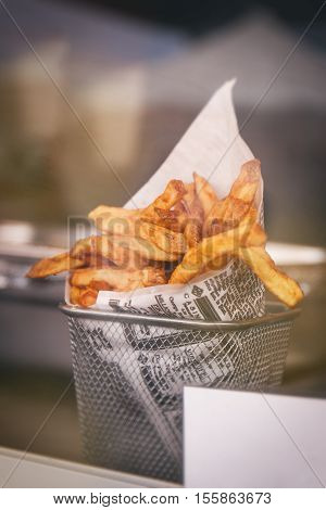 Pommes frites or french fries behind the counter window ready to eat. Street food or unhealthy food concept