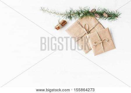 Christmas composition. Larch branches cinnamon sticks christmas gift. Flat lay top view