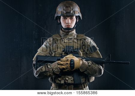 Airsoft - a game for real men. Special forces soldier with rifle on dark background. airsoft is played only real men