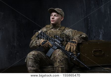The soldiers - our pride. Special forces soldier with rifle on dark background. Modern soldier with rifle