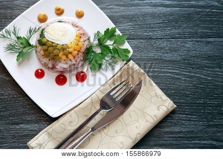 White plate with aspic near fork and knife on black table