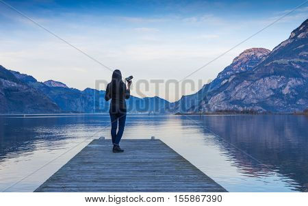 The female figure with a camera in hand on a wooden pier. Mountain landscape at sunset reflected in the lake.