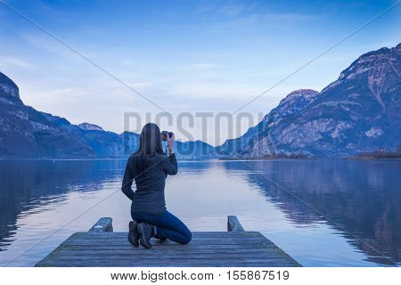 The female figure is sitting with a camera in hand on a wooden pier. Mountain landscape at sunset reflected in the lake. Clouds in the sky