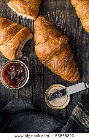 Tasty buttery croissant and jam in jar on old wooden table.
