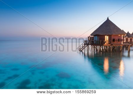 Panorama of tropical island resort with overwater bungalows at night. Ari Atoll.