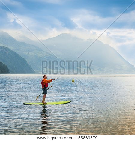 Brunnen Switzerland - June 11 2013. One man stand up padling on the lake with outstretched arm points.
