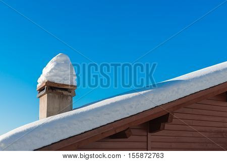 Roof the house in the snow snowbank, chimney in the snow. Blue clear sky on a cold Christmas day.