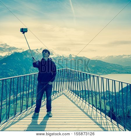 Interlaken Switzerland - April 30 2015. Young man photographing himself on a phone standing on the viewing platform in Swiss Alps. Vintage styling effect.