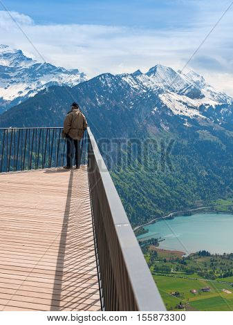 Man stands on the edge of the observation deck. Grandiose panorama on top of Bernese Oberland Interlaken and mountain range. Switzerland