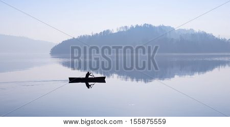 Man floating in a boat. Fog over the lake mountains reflected in the water