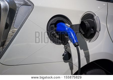 Electric Car Being Charged. Charging An Electric Car With The Power Supply Plugged In.