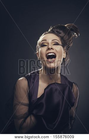 Eccentric joyful young woman with happy attitude screaming out of joy laughing out loud or singing at camera against a dark background.