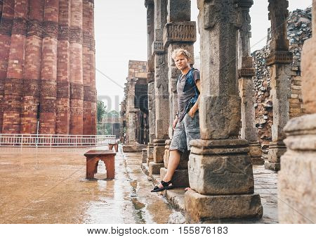 Indian monsoon season - young tourist man waits intense rain in Qutb Minar New Delhi