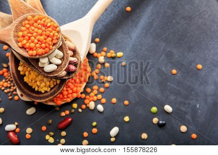 Various Raw Legumes In Wooden Spoons