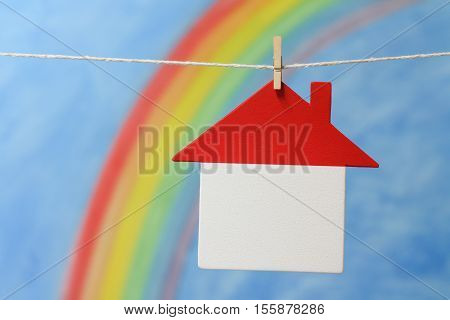 Symbol of a house with a rainbow and blue sky representing home, house, mortgage and financial loan.