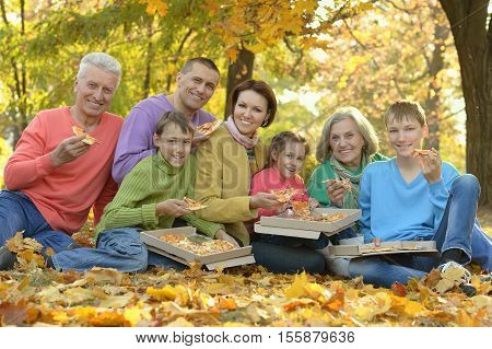 Happy family eat pizza together in autumn park