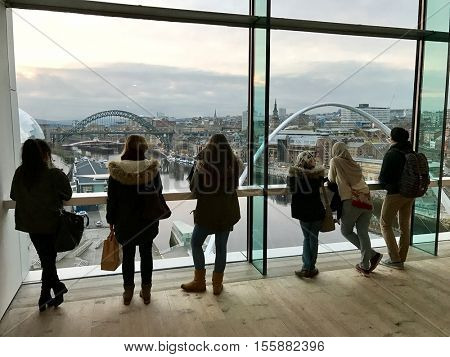NEWCASTLE - NOVEMBER 9: Visitors to The Baltic Centre for Contemporary Art view the Newcastle skyline from the viewing box on November 9, 2016 in Newcastle, UK.