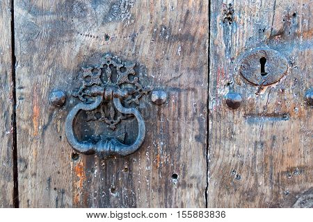 An old weathered ornate door handle and lock