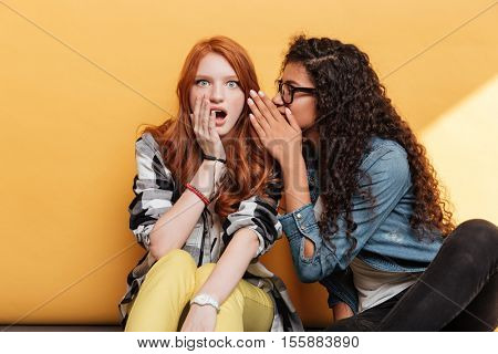 Two lovely young women talking and telling secrets over yellow background