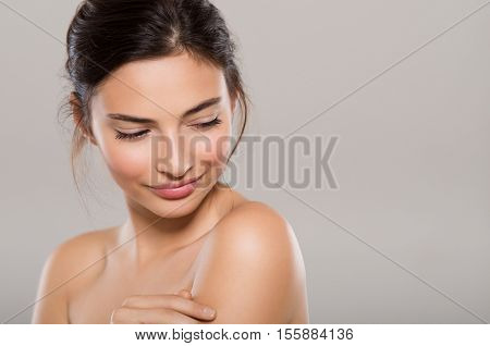 Beautiful young woman looking down and thinking with copy space. Portrait face of shy brunette girl isolated on grey background. Smiling young woman feeling skin after skin treatment.