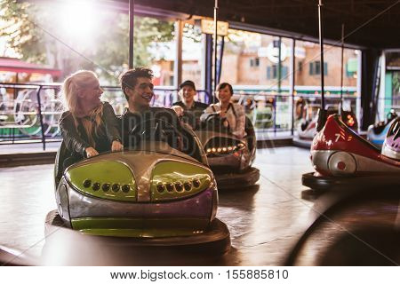 Young people driving bumper car at fairground. Young friends having fun riding bumper car at amusement park.
