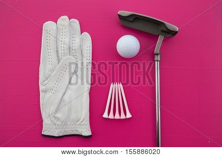 Different golf equipments on the pink desk - flat lay photography