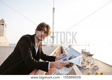 Businessman stood reading the newspaper in port