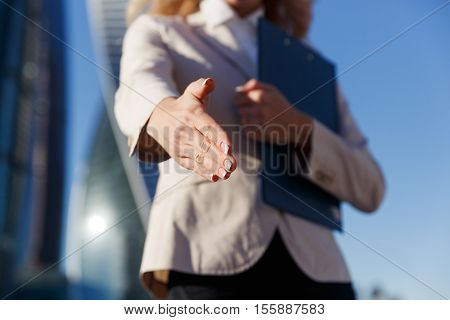 Business woman holding blue folder giving arm extended for handshake. Open hand closeup. Partnership, business, agreement concept