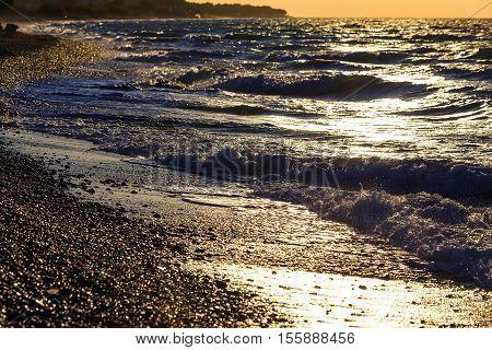 sunset on the beach with black sand. Aegean sea, pebble beach