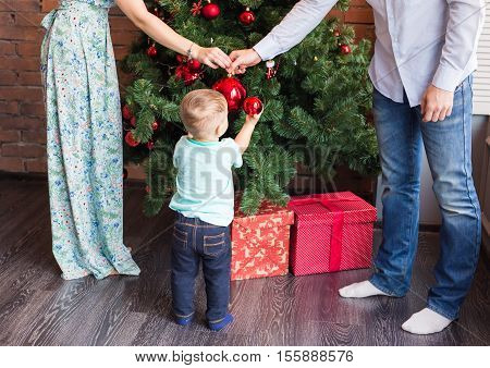 family, christmas, x-mas, winter, happiness and people concept - smiling family decorating christmas tree.