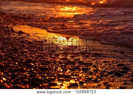pebble beach close-up with surfing sea in a sunset light