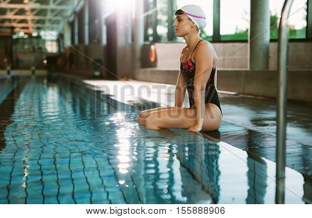 Female Swimmer Resting At The Edge Of A Pool