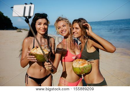 Three young women in swimsuit on the beach taking self portrait with smart phone on selfie stick. Group of female friends holding coconuts and taking selfie on the sea shore.