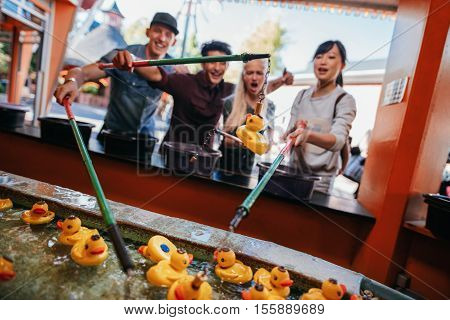 Group of people playing fishing game together at amusement park. Young people having fun at fairground.