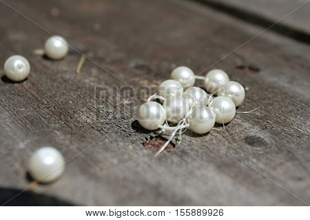 white pearls-Macro shot of a broken white pearl bracelet, wooden table background, horizontal
