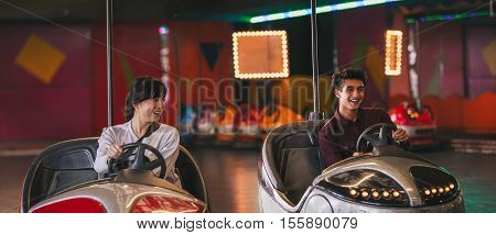 Two young friends riding bumper cars at amusement park. Happy young man and woman driving bumper cars.