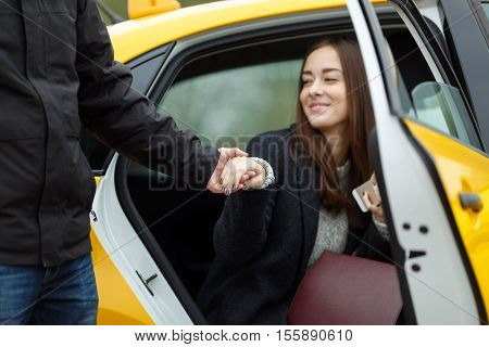 Young smiling business woman leaving the taxi. Man takes a womans hand