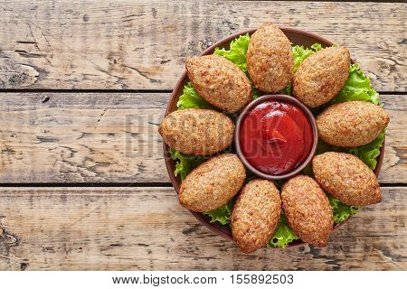 Kibbeh traditional middle eastern homemade beef, lamb, goat or camel meat stuffed bulgur kofta spicy meatball roasted croquettes on green salad food on vintage wooden table background