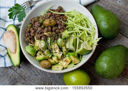 Green raw vegan zucchini pasta with lentils, pesto, tahini, avocado, olives and oil. Delicious food detox every day