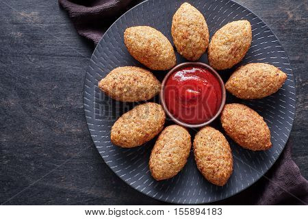 Kibbeh traditional restaurant menu middle eastern beef, lamb, goat or camel meat stuffed bulgur kofta spicy meatball fried croquettes dinner food on dark table background