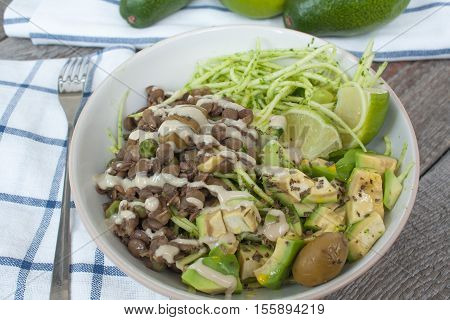 Green raw vegan zucchini pasta with lentils, pesto, tahini, avocado, olives and oil. Delicious food detox every day.